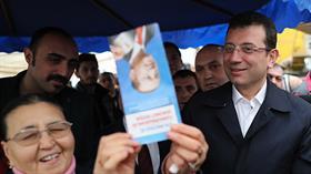Pazarda bir kadın Ekrem İmamoğlu'na Başkan Erdoğan'ın fotoğrafının bulunduğu broşürü gösterdi